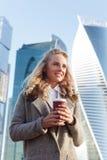 Elegante junge blonde Frau mit Kaffee vor Wolkenkratzern Lizenzfreie Stockfotos