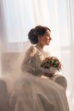 Elegante junge Braut im Hochzeitskleid, Atelieraufnahme Lizenzfreie Stockfotos