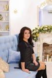 Elegante junge Brunettefrau, die das Sitzen auf Couch lächelt und aufwirft Stockbild