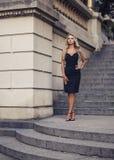 Elegante junge Frau, die draußen auf schöner Treppe steht Stockfoto
