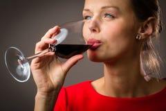 Elegante junge Frau, die ein Glas Rotwein isst Lizenzfreies Stockbild