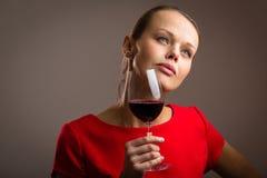 Elegante junge Frau, die ein Glas Rotwein isst Stockbild