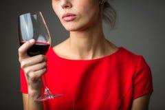 Elegante junge Frau, die ein Glas Rotwein isst Lizenzfreies Stockfoto