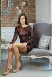 Elegante junge Frau, die im Lehnsessel sitzt lizenzfreie stockbilder
