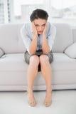 Elegante junge Frau, die mit Kopf in den Händen auf Sofa sitzt lizenzfreie stockbilder