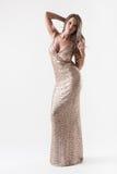 Elegante junge Frau im modernen goldenen Abendkleid stockfoto