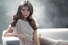 Elegante junge Frau mit ausgezeichneter klassischer Frisur Stockfoto
