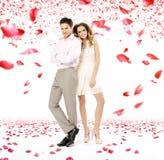 Elegante junge Paare im Blumenblattregen lizenzfreies stockbild