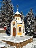 Elegante kapel met een kleine koepel met een kruis op de achtergrond van snow-covered sparren Stock Afbeelding