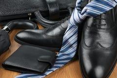 Elegante klassieke zwarte schoenen, band en paraplu, beurs en aktentas op de houten vloer Stock Foto's