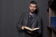 Elegante knappe modieuze mens in pak met boek Royalty-vrije Stock Foto's