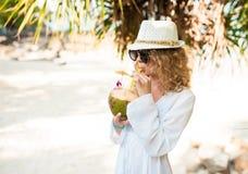 Elegante krullende vrouw met kokosnotencocktail op het strand Stock Afbeelding