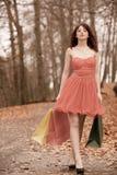 Elegante Käuferfrau, die in Park nach dem Einkauf geht Lizenzfreie Stockbilder