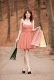 Elegante Käuferfrau, die in Park nach dem Einkauf geht Lizenzfreie Stockfotografie