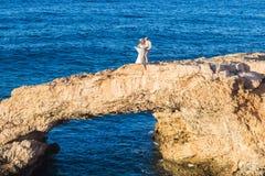 Elegante lächelnde junge Braut und Bräutigam, die auf den Strand geht, Spaß, Hochzeitszeremonie küssend und haben nahe den Felsen lizenzfreie stockbilder