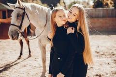 Elegante M?dchen mit einem Pferd in einer Ranch lizenzfreie stockbilder