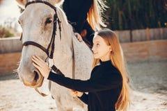 Elegante M?dchen mit einem Pferd in einer Ranch lizenzfreies stockfoto
