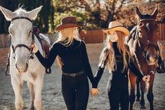 Elegante M?dchen mit einem Pferd in einer Ranch stockbild