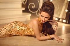 Elegante manier donkerbruine vrouw in luxe gouden kleding Haarstyl Stock Fotografie