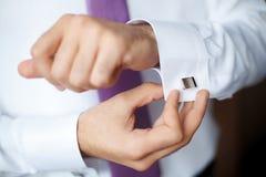 Elegante maniermens die zijn cufflinks, close-up bevestigen stock foto