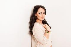 Elegante maniervrouw met juwelen dichtbij witte muur Royalty-vrije Stock Afbeelding
