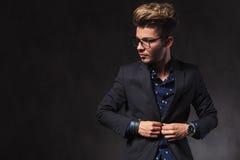 Elegante mens die glazen dragen terwijl het bevestigen van zijn jasje in donkere nagel Royalty-vrije Stock Foto