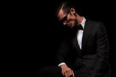 Elegante mens in zwarte dragende glazen die in dark stellen Royalty-vrije Stock Foto's
