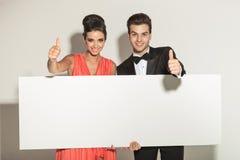 Elegante Modepaare, die ein weißes leeres Brett halten Stockbild