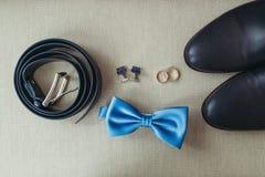 Elegante modieuze donkere mannelijke toebehoren op textuurachtergrond Hoogste mening van blouevlinderdas, schoenen, trouwringen Stock Fotografie