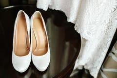 Elegante modieuze witte huwelijksschoenen op houten lijst met een kleding op achtergrond stock afbeeldingen