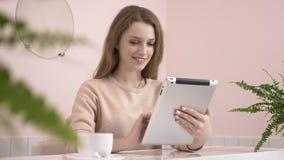 Elegante mooie Kaukasische vrouw die tabletcomputer, het texting, het typen met behulp van Glimlachend in koffie 60 fps stock video