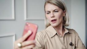 Elegante, mooie moderne vrouw die selfies op smartphone in bureaukoffie doen, wijfje met perfecte huid en modieus stock videobeelden