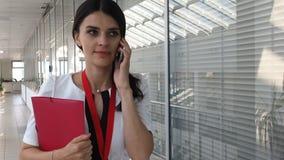 Elegante mooie vrouw die via smartphone in de bureaubouw spreken stock videobeelden