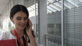 Elegante mooie vrouw die via smartphone in de bureaubouw spreken stock footage