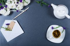 Elegante noch lebens- weiße und purpurrote Chrysanthemen, Bleistifte, Teekanne, Schale Kräutertee und Umschlag auf grauem Hinterg Stockfotografie