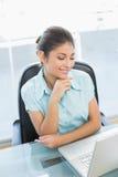 Elegante onderneemster die laptop met behulp van op kantoor Royalty-vrije Stock Foto's