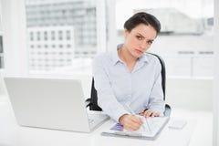 Elegante onderneemster met grafieken en laptop in bureau Royalty-vrije Stock Foto's