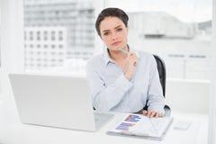Elegante onderneemster met grafieken en laptop in bureau Stock Afbeelding