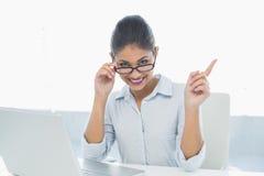Elegante onderneemster met laptop zitting bij bureau Stock Foto's