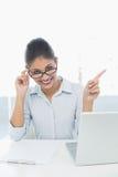 Elegante onderneemster met laptop zitting bij bureau Stock Fotografie