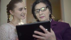 Elegante oude bedrijfsvrouw en jong meisje die een tablet op de ruimteachtergrond gebruiken stock video