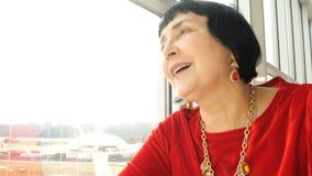 Elegante oude vrouw, het Kaukasische behoren tot een bepaald ras, die aan venster kijken stock footage