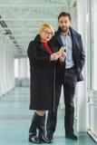 Elegante Paare kleideten im Mantel an, der am intelligenten Telefon Lobby betrachtet lizenzfreie stockbilder