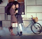 Elegante Paare mit Regenschirm am regnerischen Abend Stockbild