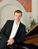 Elegante pianist naast grote piano Royalty-vrije Stock Afbeeldingen