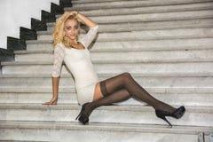 Elegante recht blonde junge Frau, die auf Marmortreppe sitzt Lizenzfreies Stockbild