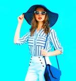 Elegante recht junge Frau, die einen Strohhut, weiße Hosen trägt lizenzfreie stockfotografie