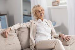 Elegante reife Frau, die auf Couch aufwirft stockfotografie