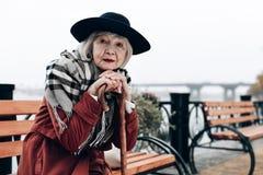 Elegante reife Frau, die auf ihrem Spazierstock sich lehnt stockbilder