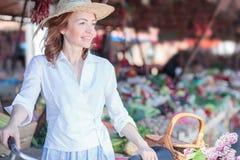 Elegante reife Frau, die durch den Freilichtmarkt, kaufend für Lebensmittelgeschäfte geht lizenzfreie stockfotos
